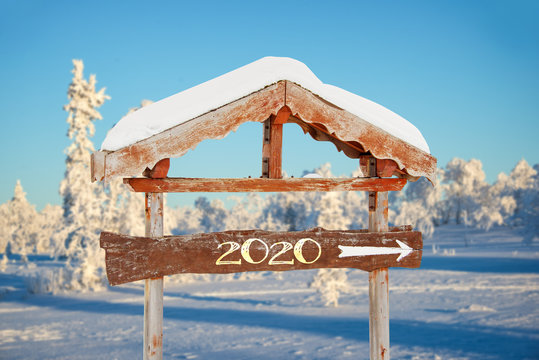 2020 written on a wooden direction sign, blue sky and winter snowy tree landscape background happy holiday seasons new year greetings