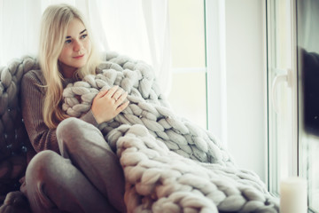 home coziness girl plaid window, home autumn look, model in a warm knitted blanket heats up