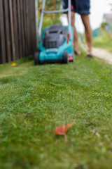 a man mows a lawn with a lawn mower