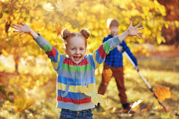 Happy red haired girl throwing leafs in the air