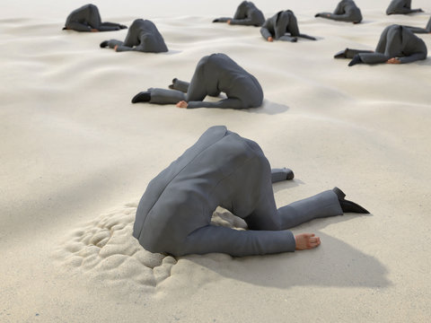 group of businessmen hides their heads in the sand
