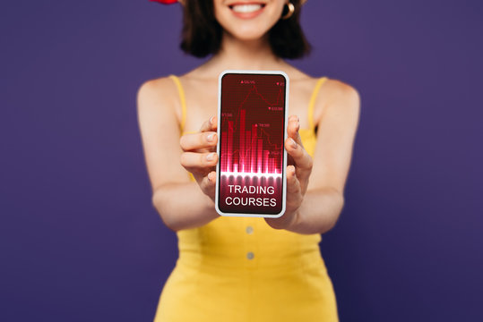 selective focus of smiling girl presenting smartphone with trading courses app isolated on purple