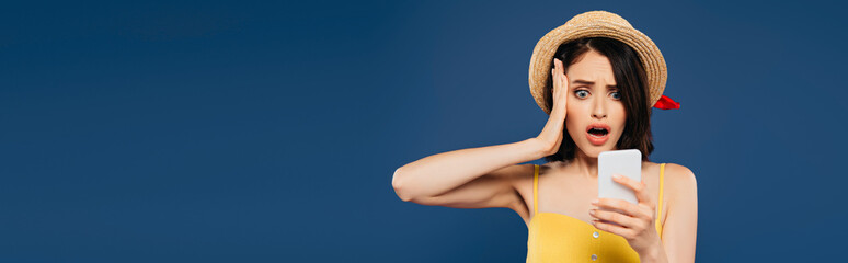 panoramic shot of shocked pretty girl in straw hat using smartphone isolated on blue