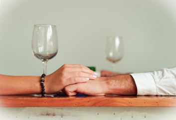 Closeup of couple hands on restaurant table with . Romantic couple holding each other's hand at dinner in a luxury restaurant. Marriage proposal and engagement concept. Focus on the hands - Image