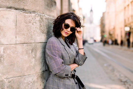 Attractive fashion modern woman in sunglasses standing on the city street. Summer portrait of happy girl on a walk