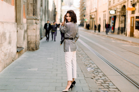 Attractive modern woman standing on the city street. Young beautiful girl in stylish elegant clothes walking at sunset along the streets of the city.