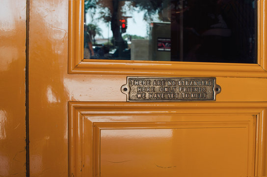 """Yellow wooden door of an irish pub in Seville with a banner """"There are no strangers here, only friends we have yet to meet"""""""