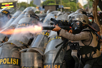 A riot police officer fires tear gas during a riot following protests near Indonesian Parliament building in Jakarta