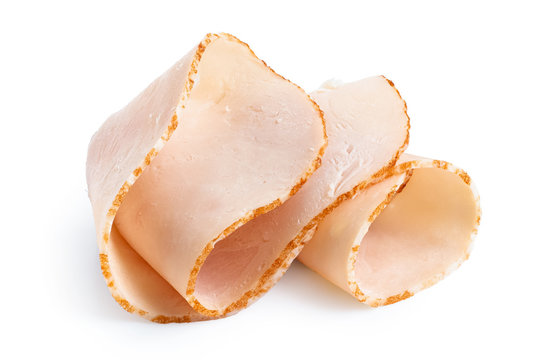 A folded single slice of chicken ham isolated on white.
