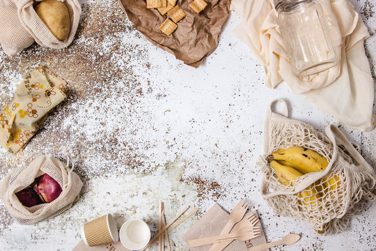 Bowls, dishes, glasses, forks, napkins, different plastic free tableware, shopping bag, glass canister and bees wrap reutilizable displayed around a table with different ingredients, coffe and milk