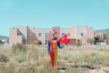 scary clown with a bunch of balloons outdoors