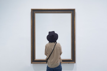 interior view of a lonely girl or tourist looking at blank canvas at a museum or gallery. Fototapete