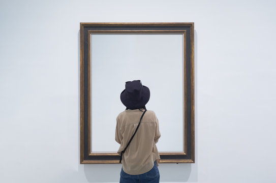 interior view of a lonely girl or tourist looking at blank canvas at a museum or gallery.