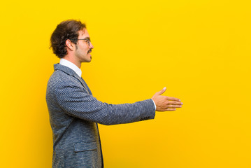 young handsome man smiling, greeting you and offering a hand shake to close a successful deal, cooperation concept against orange wall