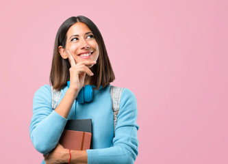 Young student girl with blue sweater and headphones standing and thinking an idea on pink background