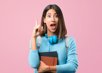 Young student girl with blue sweater and headphones standing and thinking an idea pointing the finger up on pink background