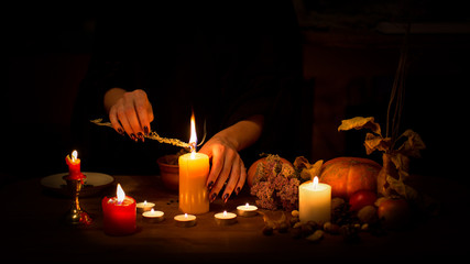 Witch make a spell on the altar in the dark. Female hands with sharp black nails burning magic herb among candles, pumpkin, nuts, dry leaves, selected focus, low key