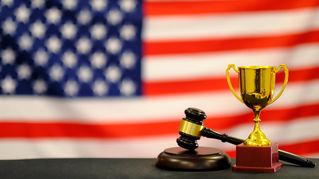 Judge's gavel and trophy USA flag. Symbol for jurisdiction. Law concept a wooden judges gavel on table in a courtroom or law enforcement office