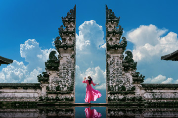 Wall Murals Bali Young woman standing in temple gates at Lempuyang Luhur temple in Bali, Indonesia. Vintage tone.