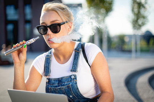 Modern woman smoking e-cigarette and using her laptop computer while sitting at street