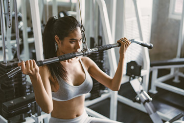 young fitness woman execute exercise with exercise-machine in gym, horizontal photo.Doing Workout Exercises.Relaxing After Fitness Training in gym. Fototapete