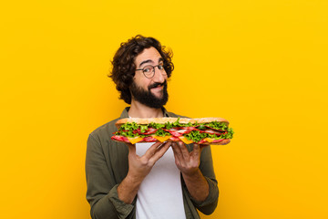 Foto op Canvas Snack young crazy bearded man with a giant sandwich.