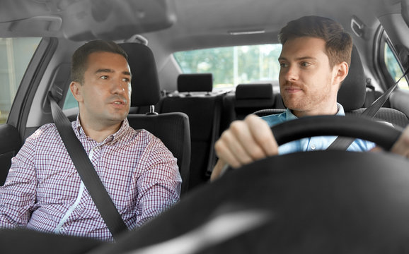 car driving lesson and carpooling concept - instructor on passenger seat and young driver talking