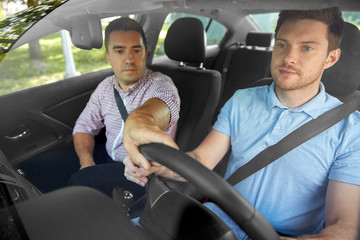 driver courses and people concept - car driving school instructor teaching young man to drive Fototapete