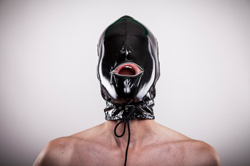 man with latex mask on head isolated on gray background open mouth