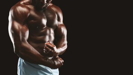 Strong biceps and chest of black bodybuilder