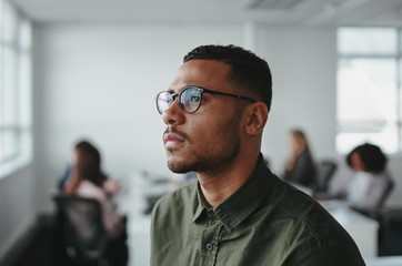 Close-up of a young african american business man entrepreneur wearing eyeglasses contemplating in office Fototapete