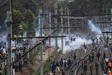 Protesters run through rail way as riot police fire tear gas during a riot following protests near Indonesian Parliament building in Jakarta