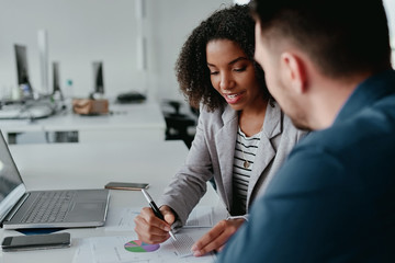 Close-up of young female executive discussing business plan to her colleague with graph and chart on desk
