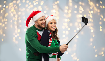 christmas, technology and holidays concept - happy couple in santa hats taking picture by smartphone on selfie stick at ugly sweater party over festive lights background