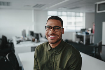 Fototapeta Friendly and smiling young african american professional businessman looking at camera in modern office obraz