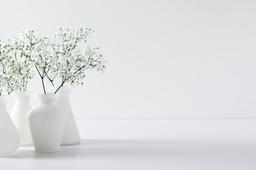 Foto op Canvas Bloemenwinkel Home interior floral decor. Elegant floral soft white composition. Beautiful white gypsophila flower in vase on white wall background.