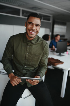 Portrait of a smiling young businessman holding digital tablet in hand looking to camera and colleague at background