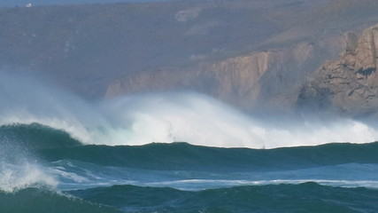 White horses riding electric blue waves at Sennen