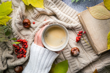Female hands holding hot coffee, blanket and autumn leaves on autumn background. Vintage toning. autumn relax concept