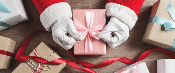 Santa Claus hands with group of gift boxes.