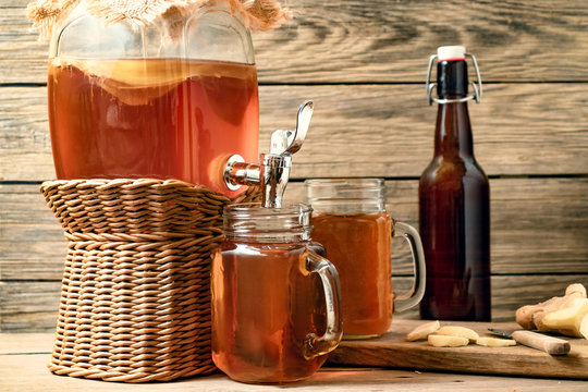 Fresh homemade Kombucha fermented tea drink in jar with faucet and in cans-mugs on wooden background