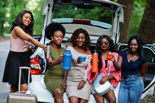 Group of five happy african american traveler girls sitting in car open trunk and drink tea from thermos.