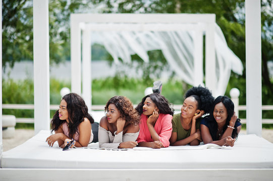 Group of five african american girls relaxing at beautiful poolside cabana beside luxury resort.