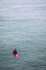 Man on surfboard in calm ocean