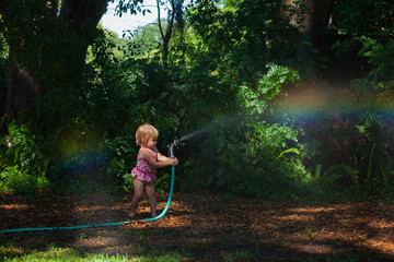 A little girl playing with a hose making rainbows with a hose