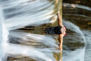 Woman inside waterfall flow