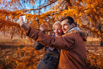 Adult son taking selfie with his mother using smartphone in autumn park. Family time