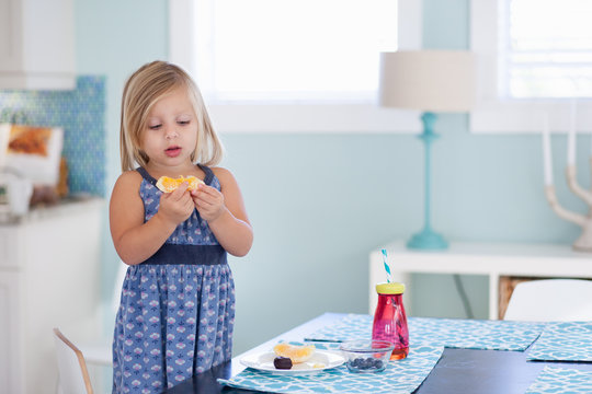 A little girl at her kitchen table having a healthy snack