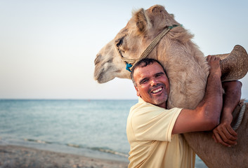 Camel owner on the coast of Tunisia with his camel, close-up