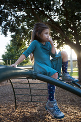 A little girl sitting atop a jungle gym outside at a playground